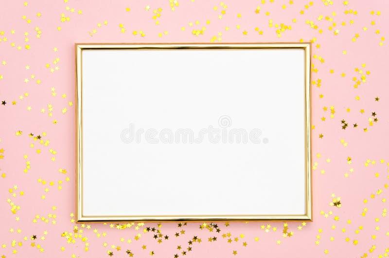 Насмешка рамки фото вверх с космосом для текста, золотого confetti sequins на розовой предпосылке Положение плоское, взгляд сверх стоковое фото rf