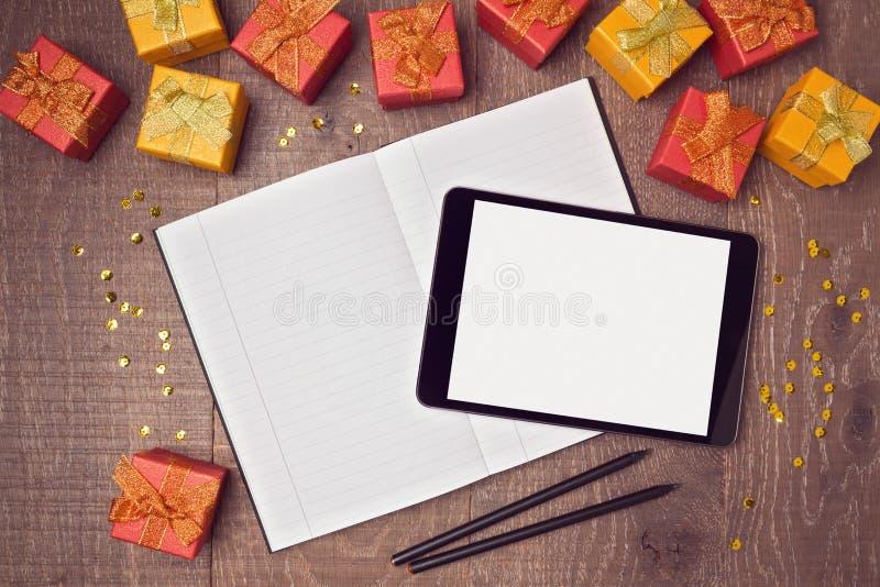 Насмешка таблетки цифров вверх по шаблону с подарочными коробками и тетрадью на деревянном столе над взглядом стоковая фотография rf