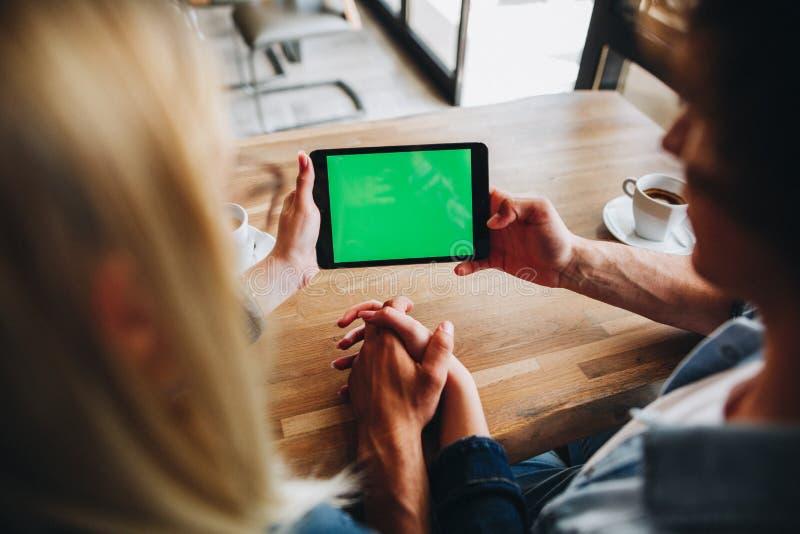 Насмешки экран вверх - зеленый на приборе таблетки, молодой паре наблюдая t стоковое изображение rf