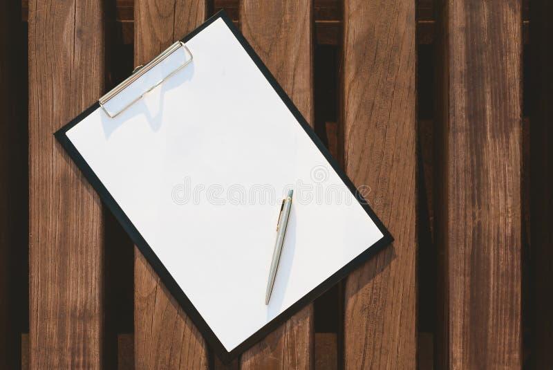 Насмешливый вверх планшета для бумаги на предпосылке деревянной стены стоковое изображение rf