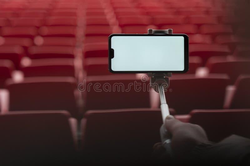 Насмешливый поднимающий вверх смартфон с ручкой selfie в руках человека на предпосылке стоек Парень принимает selfie на стоковое фото