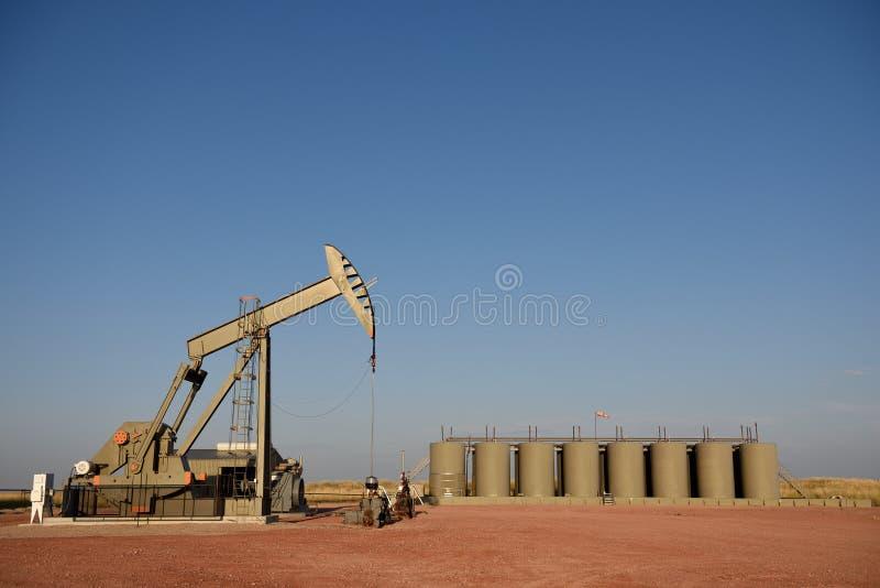 Насос места нефтяной скважины сырой нефти поднимают домкратом и баки для хранения продукции в сланце Niobrara стоковые фотографии rf