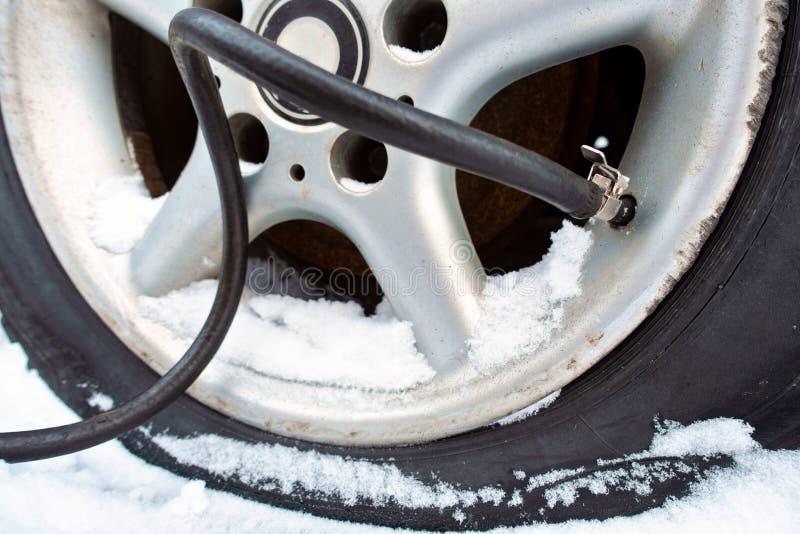 Насос нагнетает воздух в автошину в зиме стоковое фото