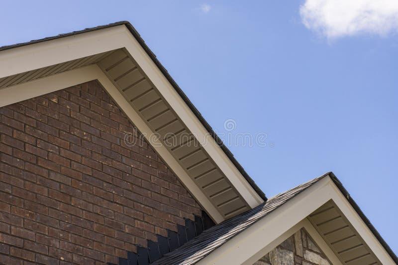 Настелите крышу показывать soffit на фронте дома кирпича стоковое изображение