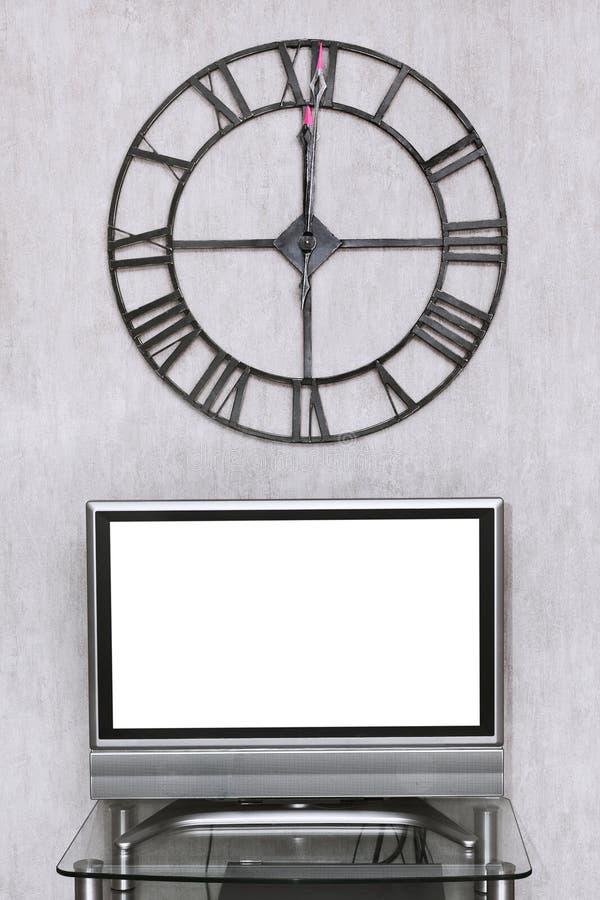 Настенные часы под пустым белым экраном телевизора стоковые фотографии rf