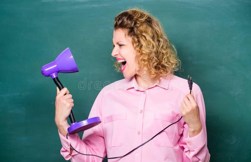 Настольная лампа владением учителя в предпосылке доски руки e Осветите вверх процесс изучать Проницательность и идея стоковое изображение