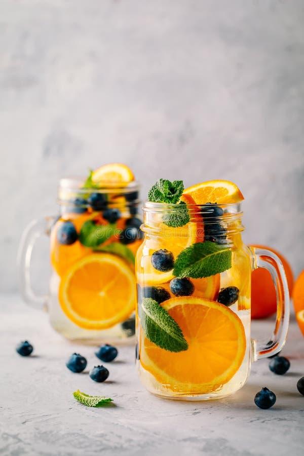 Настоянная вода вытрезвителя с апельсином, голубикой и мятой Лед - холодные коктеиль или лимонад лета стоковая фотография rf