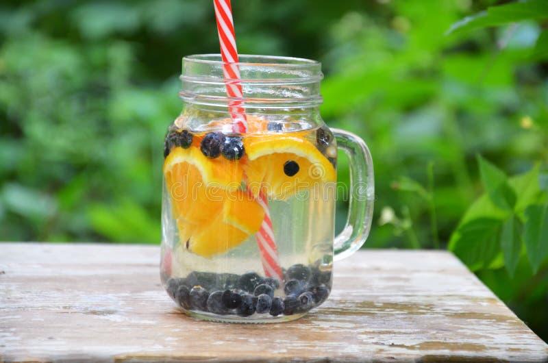 Настоянная вода вытрезвителя с голубикой, клубникой, апельсином и мятой Лед - холодные коктейль или лимонад лета в стеклянном опа стоковое изображение rf