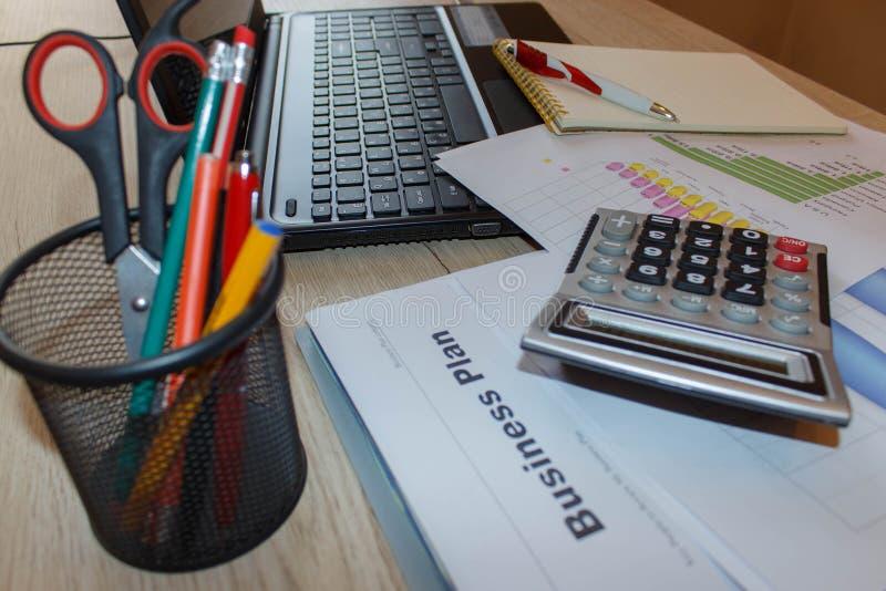 Настольный компьютер дела с компьтер-книжкой, калькулятором и финансовыми отчетами, взгляд сверху стоковая фотография rf