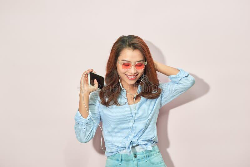 Настроение лета портрета счастливое радостной молодой женщины с длинным вьющиеся волосы, в солнечных очках на светлой предпосылке стоковые фото
