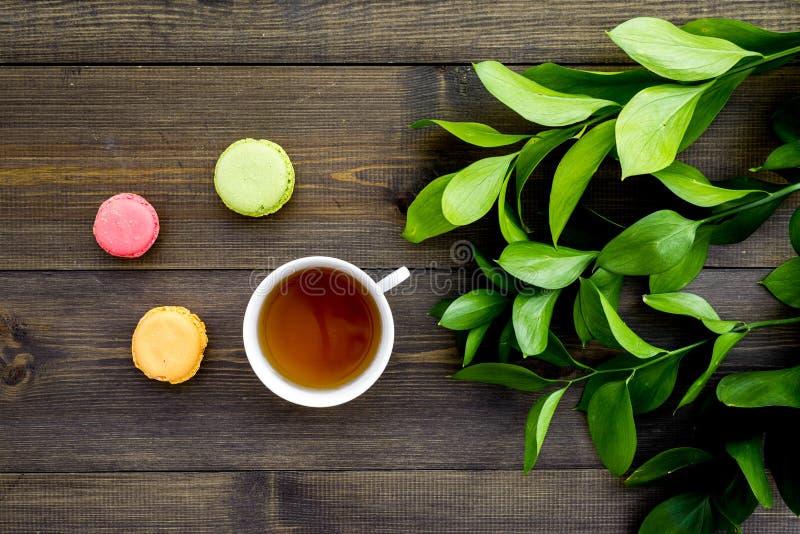 Настроение лета, чаепитие лета Macarons чашки чаю и помадок приближают к растительности brignt на темном деревянном взгляд сверху стоковое изображение
