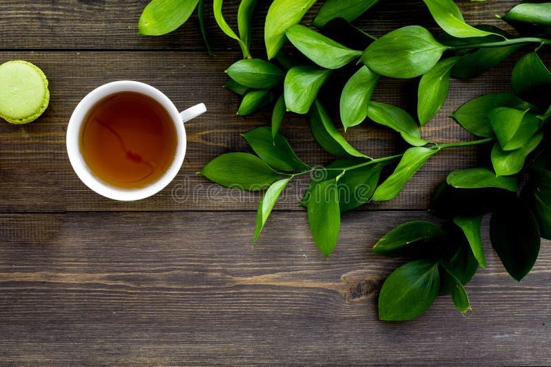 Настроение лета, чаепитие лета Macarons чашки чаю и помадок приближают к растительности brignt на темном деревянном взгляд сверху стоковые изображения