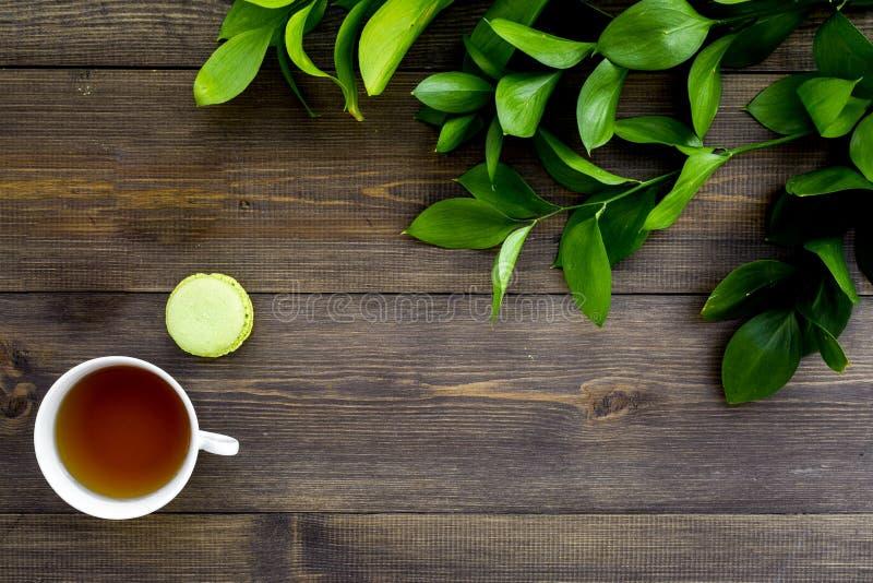 Настроение лета, чаепитие лета Macarons чашки чаю и помадок приближают к растительности brignt на темном деревянном взгляд сверху стоковое фото rf