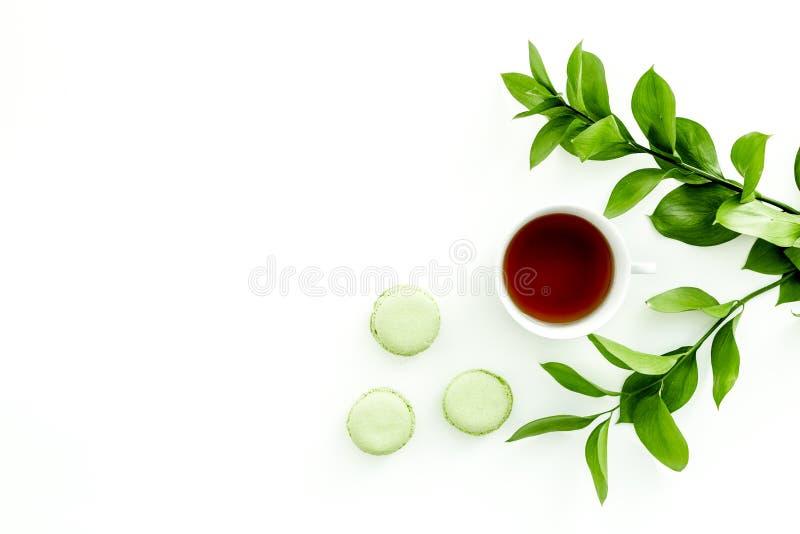 Настроение лета, чаепитие лета Macarons чашки чаю и помадок приближают к растительности brignt на белом экземпляре взгляд сверху  стоковое изображение