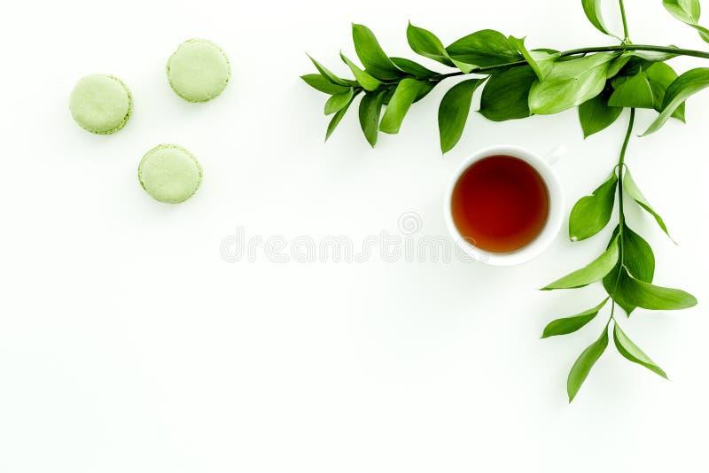 Настроение лета, чаепитие лета Macarons чашки чаю и помадок приближают к растительности brignt на белом экземпляре взгляд сверху  стоковое изображение rf