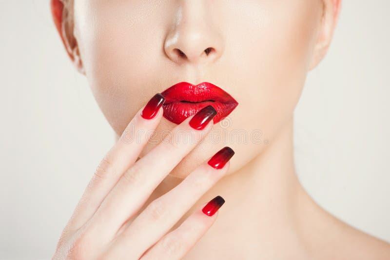 Настройка макияжа и маникюр макро обрезанное изображение красивого градиента красной черной маникюры и помады, изолированное на б стоковое изображение