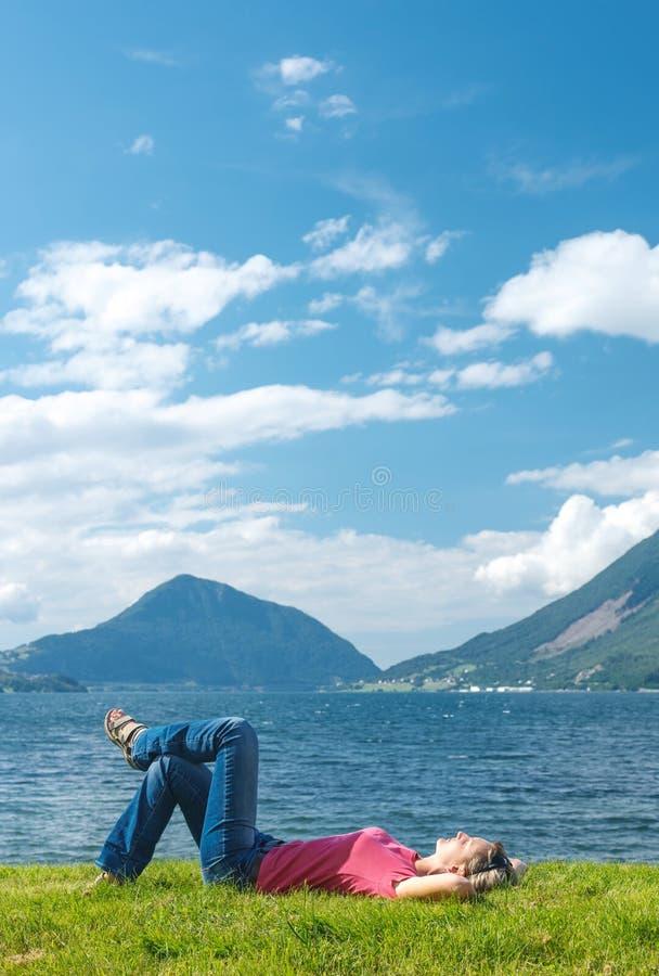 Наслаждаться женщины ослабляя на побережье фьорда стоковое фото