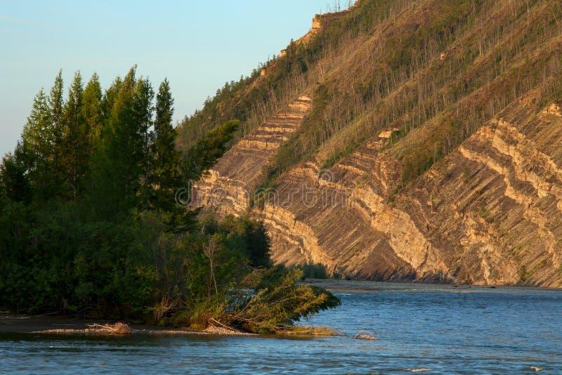 Наслоенные утесы на горном склоне над рекой стоковое фото
