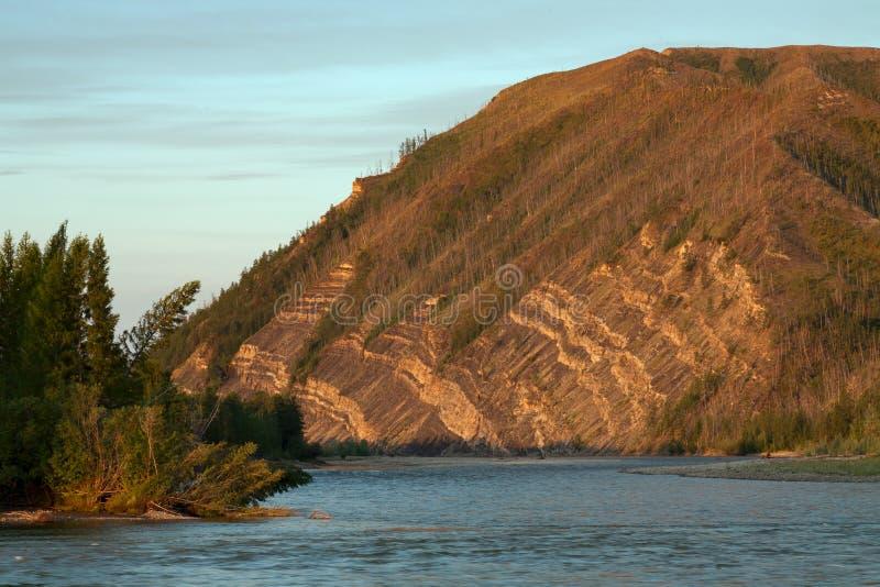 Наслоенные утесы на горном склоне над рекой стоковые изображения rf