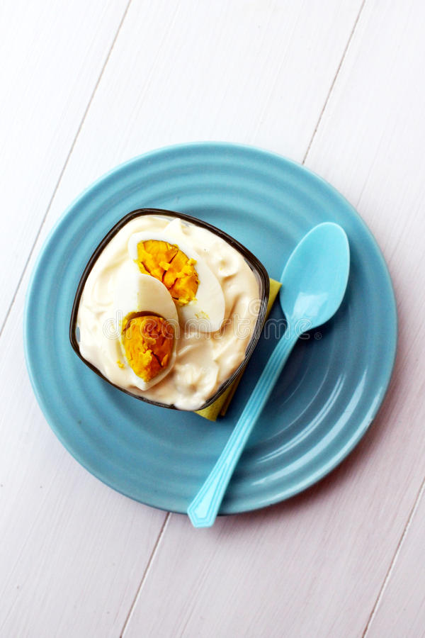 Наслоенный русский салат в стекле с трудным вареным яйцом на голубой плите стоковые фото