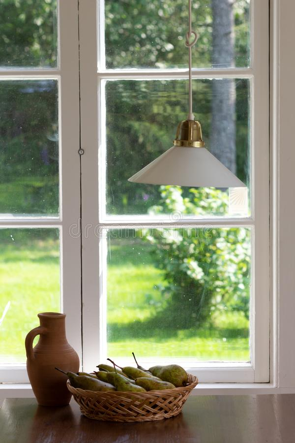 Натюрморт глиняного горшка и груш в плетеной корзине на деревянном столе около окна без занавесов стоковые изображения