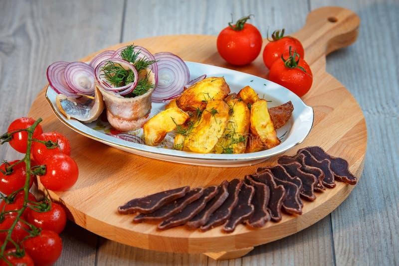 Натюрморт - закуска для пива, вылеченного мяса, деревенских картошек стоковое фото