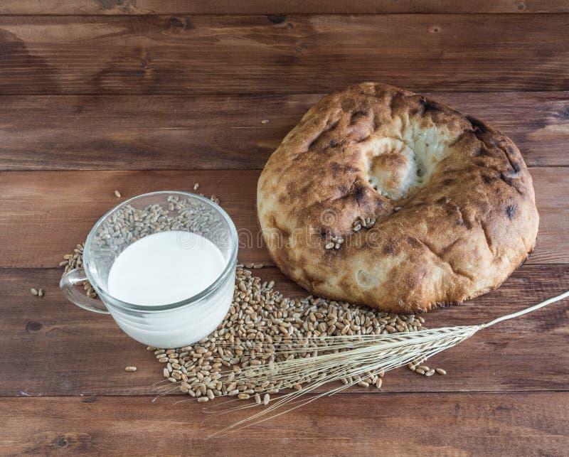 Натюрморт испеченных lavash, ушей пшеницы, зерен и кружек молока стоковые изображения rf