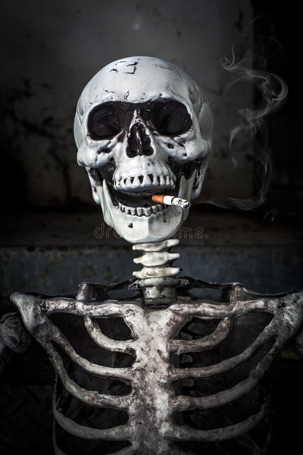 Натюрморт куря человеческий скелет с сигаретой стоковые фото