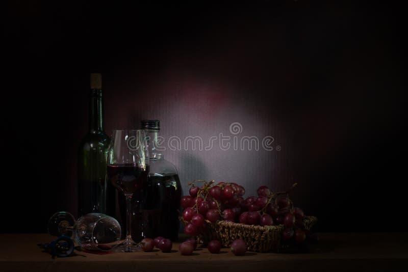 Натюрморт, лоза виноградины с вином на деревянном столе стоковые фотографии rf