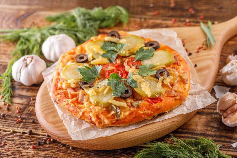 Натюрморт очень вкусный, горячая домодельная пицца с зелеными цветами на деревянной доске на таблице Очень вкусная, свежая домоде стоковые фотографии rf