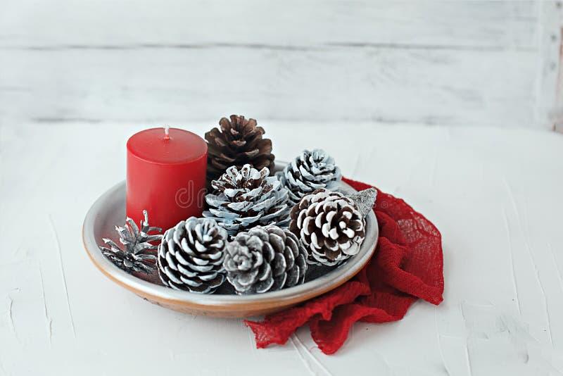 Натюрморт рождества зимы с конусами свечи и ткань serviette на белой предпосылке стоковые фотографии rf