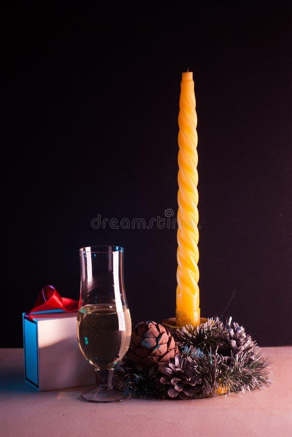 Натюрморт рождества на черной предпосылке, желтая свеча, стоковые фото