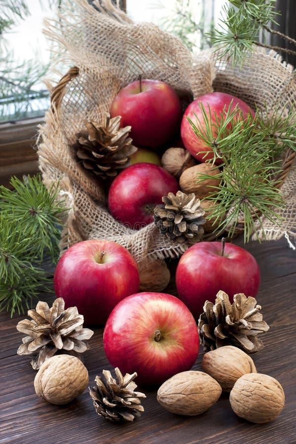 Натюрморт рождества с яблоками, грецкими орехами и конусами сосны на деревянном окне стоковые изображения rf