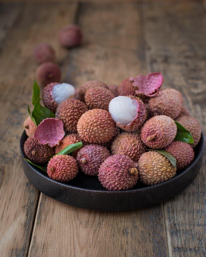 Натюрморт свежего lychee приносить в черной плите на деревянной предпосылке стоковые изображения