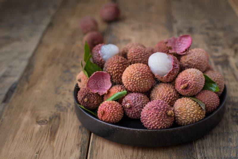 Натюрморт свежего lychee приносить в черной плите на деревянной предпосылке стоковое фото rf