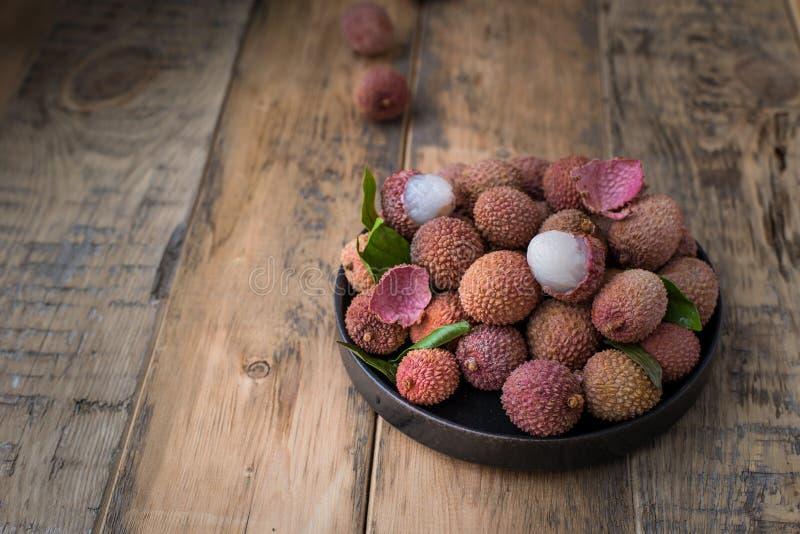 Натюрморт свежего lychee приносить в черной плите на деревянной предпосылке стоковое изображение rf