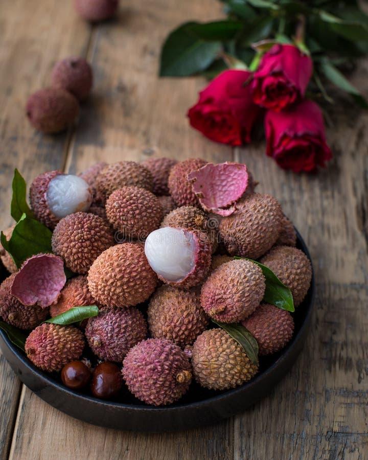 Натюрморт свежего lychee приносить в черной плите на деревянной предпосылке Деревенский тип стоковые фото