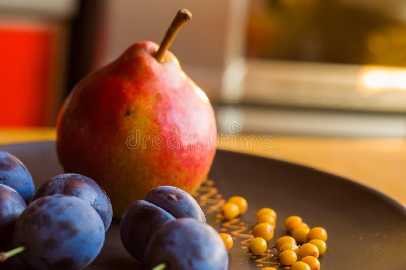 натюрморт - сочные голубые сливы, большая зрелая груша, и ягоды крушины моря в керамической плите на деревянной предпосылке стоковые изображения