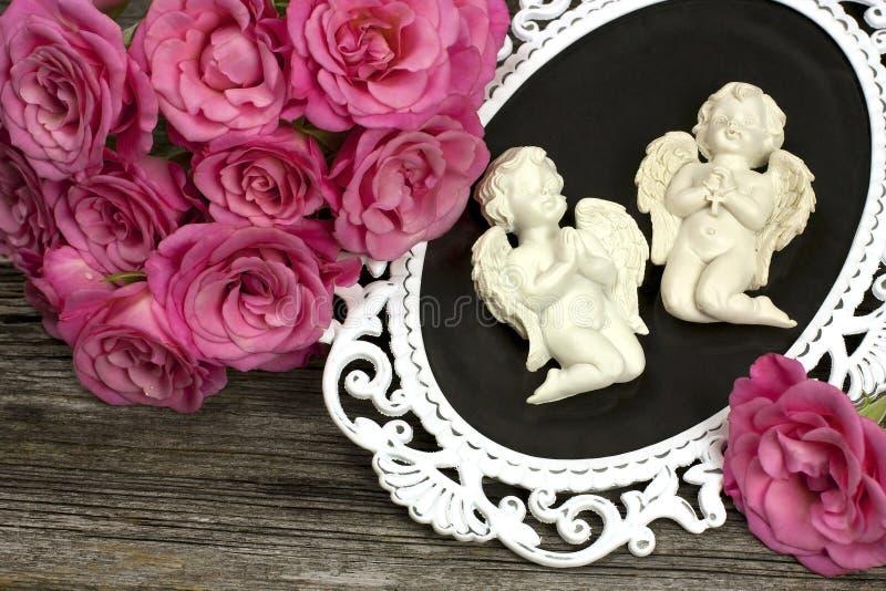 Натюрморт с ангелами и цветками стоковое фото