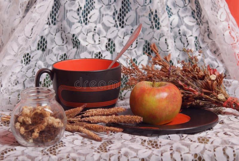 Натюрморт с большой кружкой, яблоком и высушенными травами стоковое фото