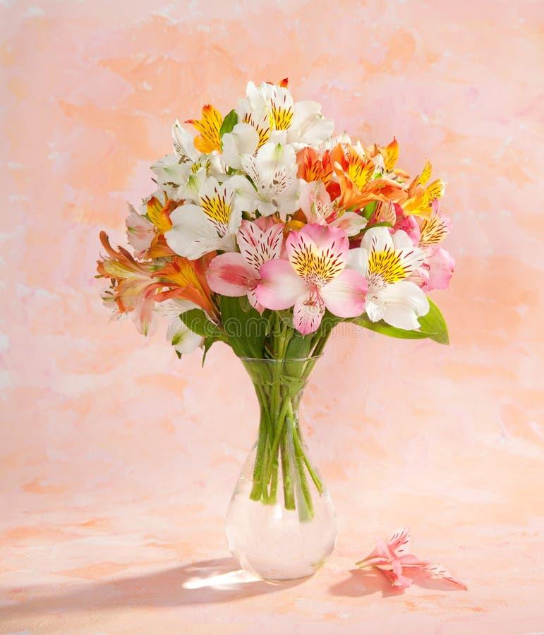 Натюрморт с букетом красочного Alstroemeria цветет в прозрачной стеклянной вазе на абстрактной предпосылке стоковое изображение rf