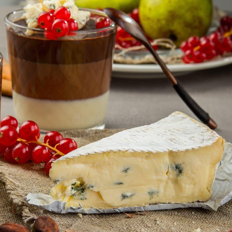 Натюрморт с голубым сыром, наслоенным десертом шоколада в стекле, клюквой и грушей стоковые фотографии rf