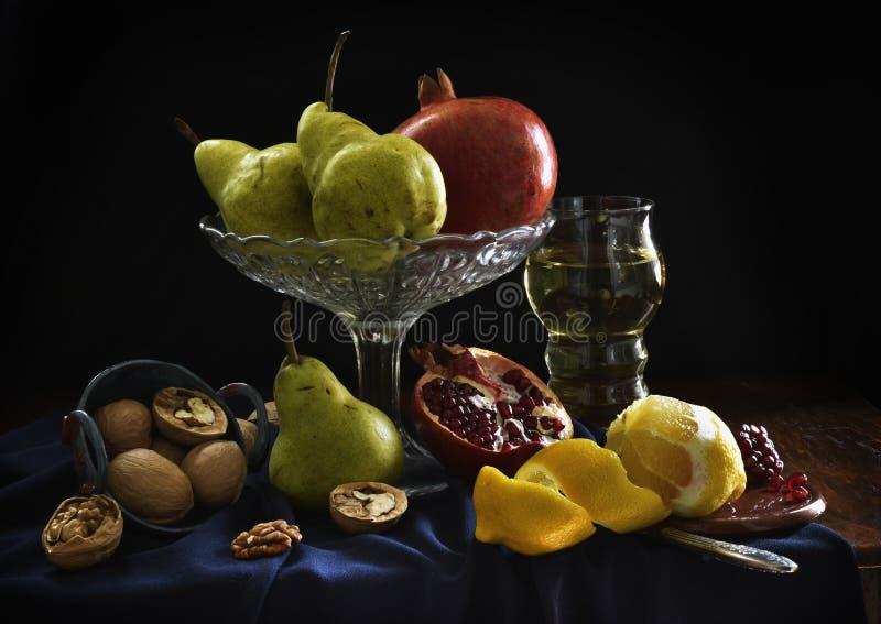 Натюрморт с гранатовым деревом, лимоном, бокалом вина, грушей, грецким орехом Темные тени, плоды в стиле голландских художников стоковые изображения