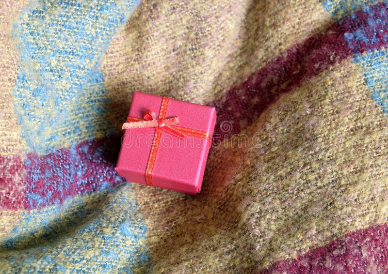 Натюрморт с праздничным подарком в малой коробке красного цвета, покрытой с лентой с смычком, против предпосылки шерстяной ткани стоковое фото