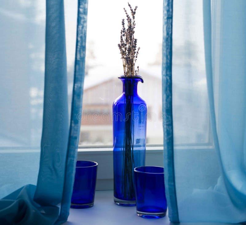 Натюрморт с синими стеклами и ваза стоя на windowsill в ландшафте зимы стоковое изображение