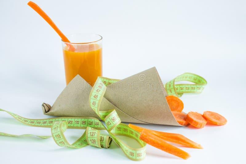 Натюрморт с соком моркови в стекле и частях морковей на белой предпосылке стоковые изображения