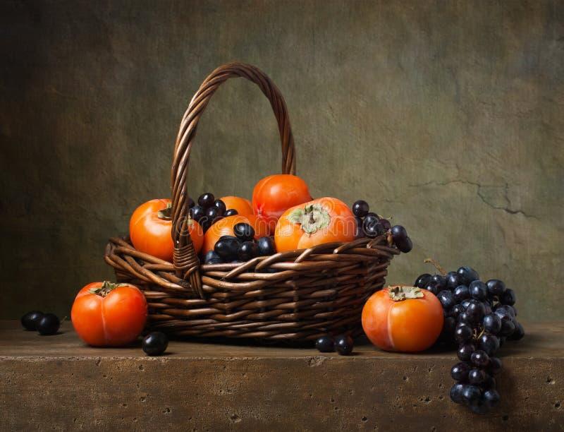 Натюрморт с хурмами и виноградинами стоковые фотографии rf