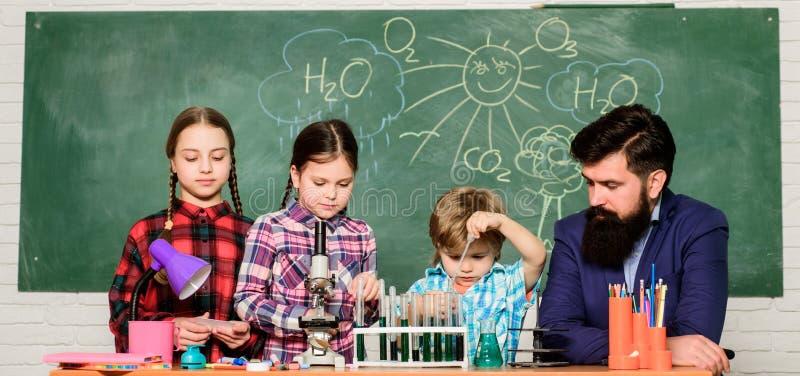 Наука включает теорию Эксперимент по химии школы Объяснять химию детям Завораживающий урок химии r стоковые фото