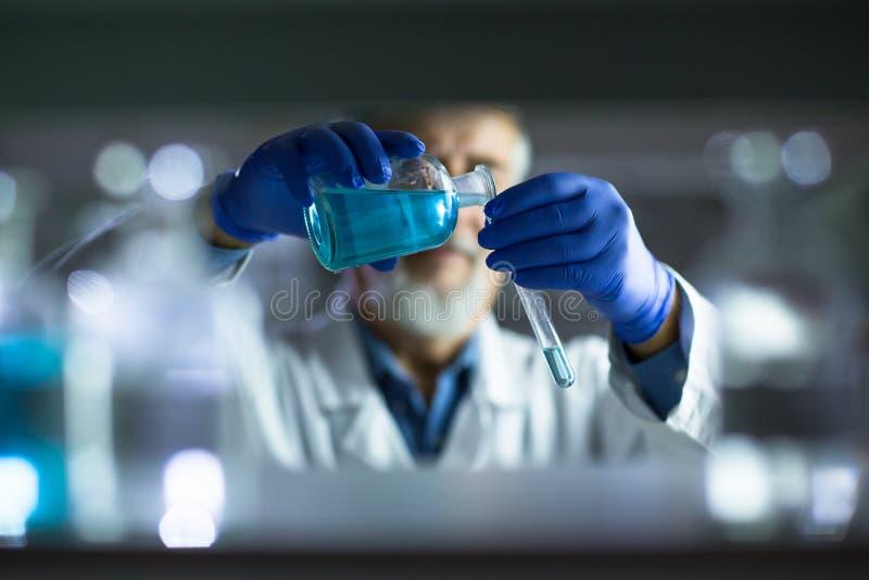 Научное исследование старшего мужского исследователя унося в лаборатории стоковые изображения rf