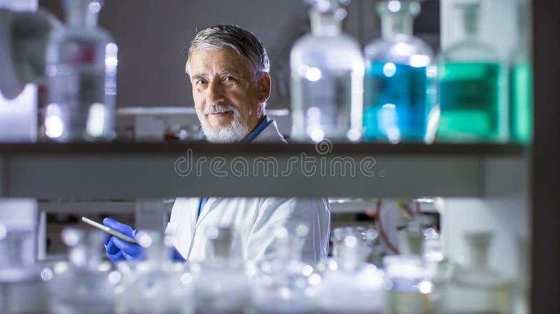 Научное исследование старшего мужского исследователя унося в лаборатории стоковые изображения